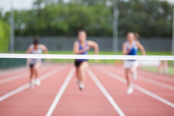 Female athletes running towards finish line on track field.jpeg