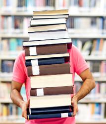 Male student carrying heavy books at the library