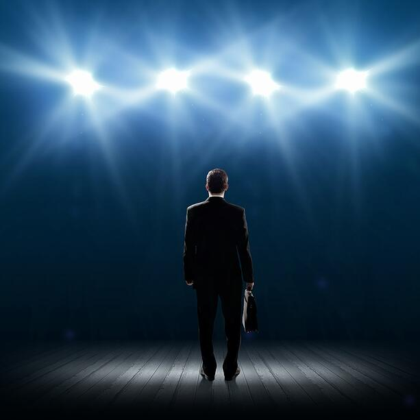 Rear view of businessman standing in lights of stage.jpeg