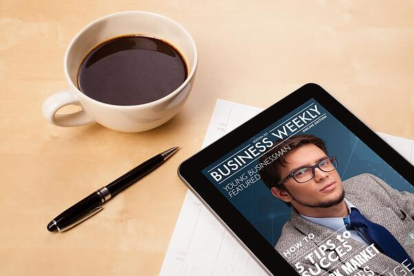 Workplace with tablet pc showing magazine cover and a cup of coffee on a wooden work table close-up.jpeg