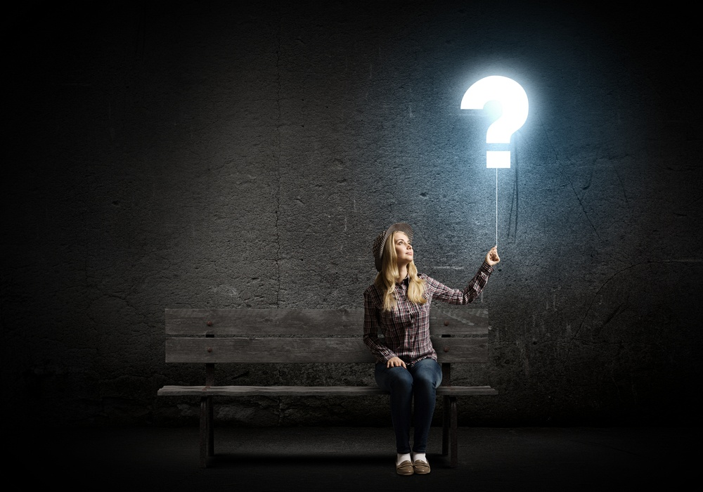 Young woman in casual holding balloon shaped like question mark.jpeg