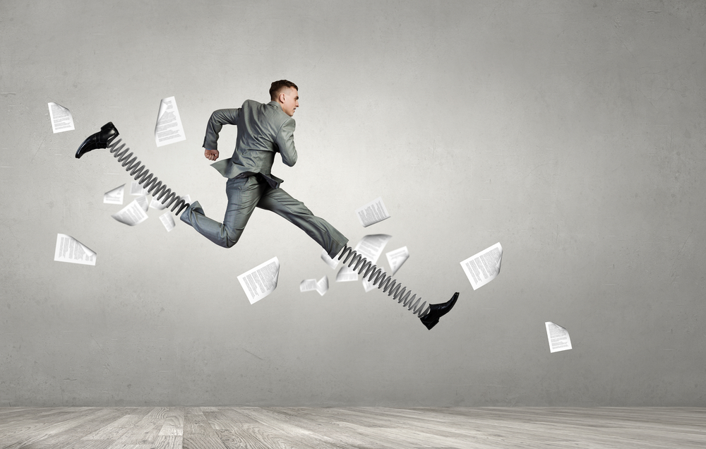 Businessman in suit jumping with big springs on feet
