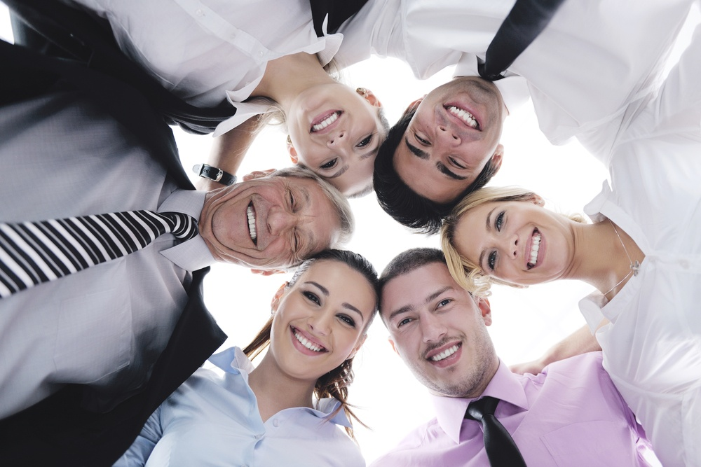 Closeup of happy business people with their heads together representing concept of ftiendship and teamwork isolated on white background.jpeg